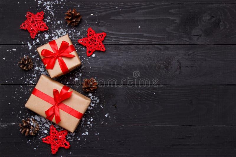 Composi??o do Natal Presentes do Natal com as estrelas decorativas vermelhas do rattan e cones no fundo preto de madeira ano novo imagens de stock