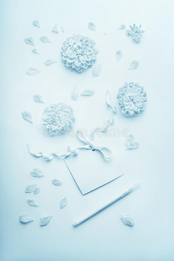 Composición azul en colores pastel de la turquesa con las flores, tarjeta de papel en blanco con la cinta y lápiz, endecha plana, fotografía de archivo