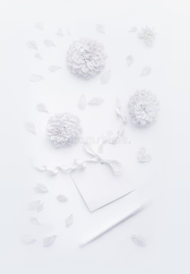 Composición blanca con las flores, tarjeta de papel en blanco con la cinta y lápiz, endecha plana, visión superior Mofa para arri imagen de archivo