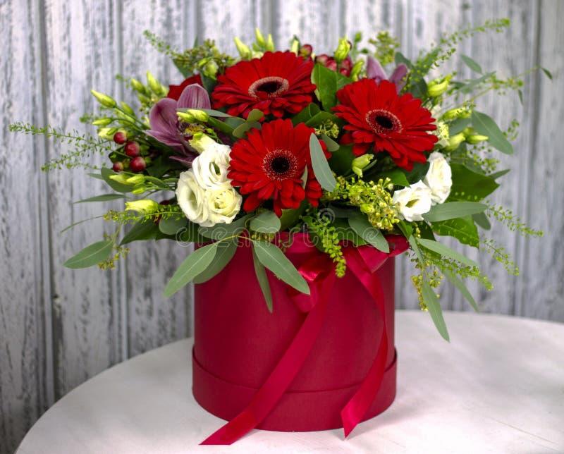 Composición brillante con los gerberas rojos en una caja del sombrero imagenes de archivo