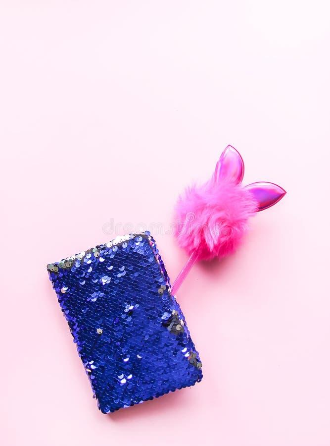 Composición brillante de los complementos Libreta de las lentejuelas del brillo y pluma adornada divertida Objetos en fondo en co foto de archivo libre de regalías