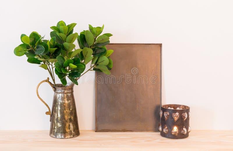 Composición casera de la decoración del vintage con los objetos del metal y plan verde fotografía de archivo libre de regalías