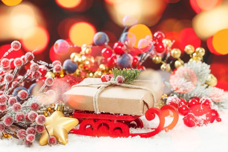 Composición colorida de la Navidad con el trineo rojo de Navidad y regalo contra fondo abstracto brillante de la luz del bokeh imagenes de archivo