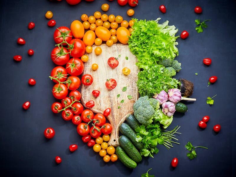 Composición colorida de las verduras con los tomates rojos y amarillos, pepinos, verdes Visi?n superior fotografía de archivo