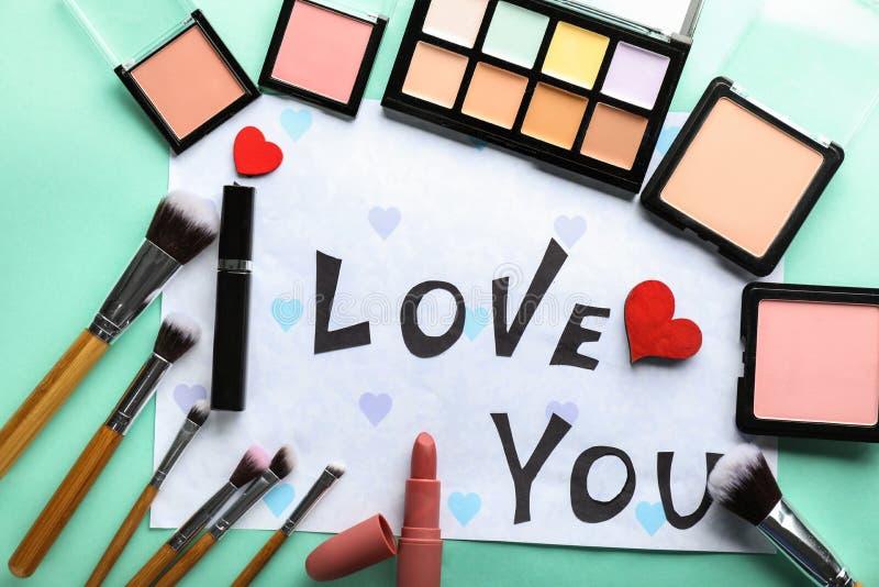 Composición con AMOR de la frase USTED y cosméticos decorativos en fondo del color foto de archivo libre de regalías