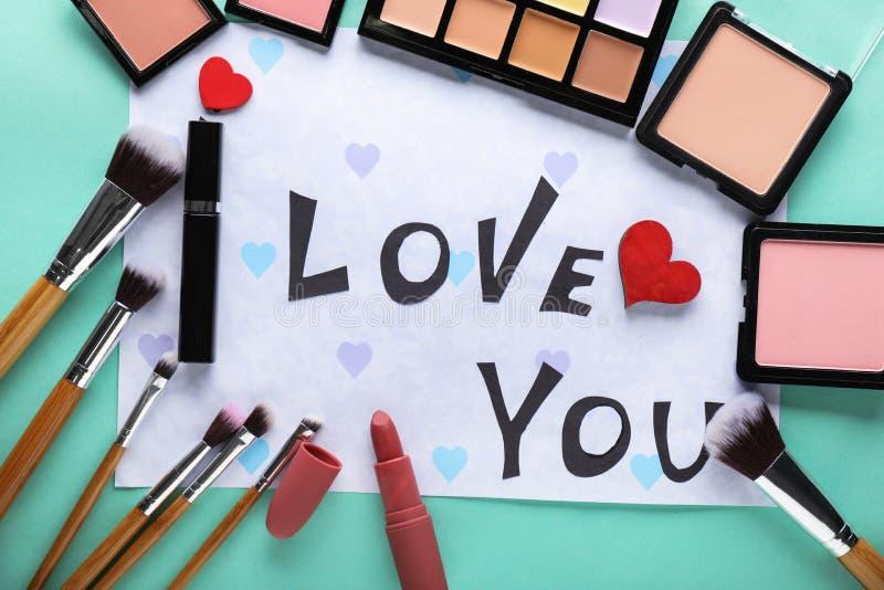 Composición con AMOR de la frase USTED y cosméticos decorativos en fondo del color imágenes de archivo libres de regalías