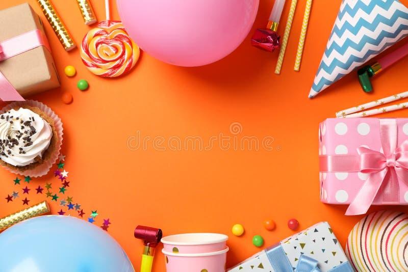 Composición con cajas de regalo y accesorios de b-día sobre fondo naranja fotografía de archivo