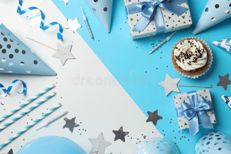 Composición con cupcake y accesorios de cumpleaños con dos tonos de fondo fotografía de archivo libre de regalías