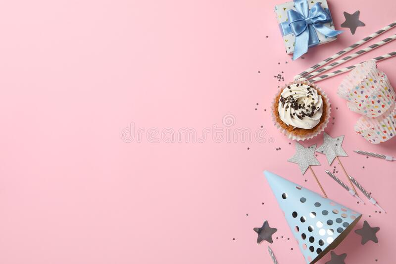 Composición con cupcake y accesorios de cumpleaños en fondo rosa fotos de archivo libres de regalías
