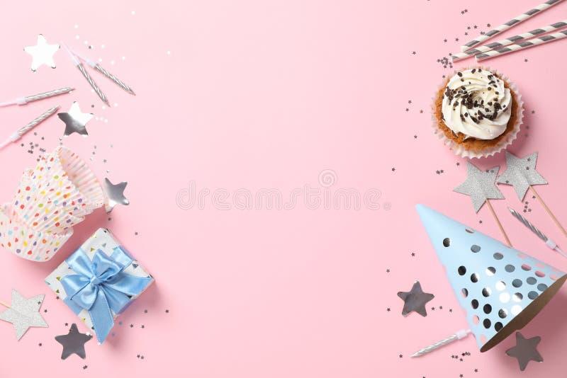 Composición con cupcake y accesorios de cumpleaños en fondo rosa imagenes de archivo