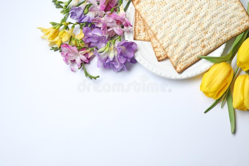 Composición con el matzo y las flores en el fondo blanco, visión superior imagen de archivo