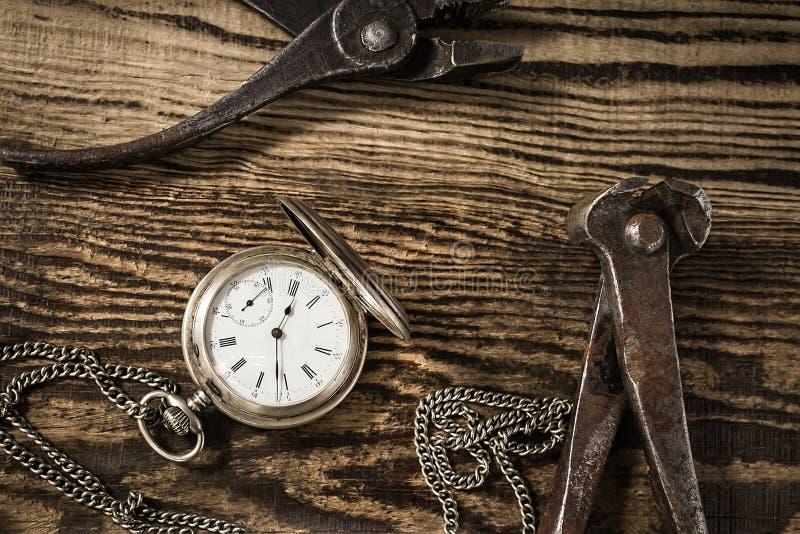 Composición con el reloj de bolsillo del vintage Herramientas y reloj viejos fotografía de archivo