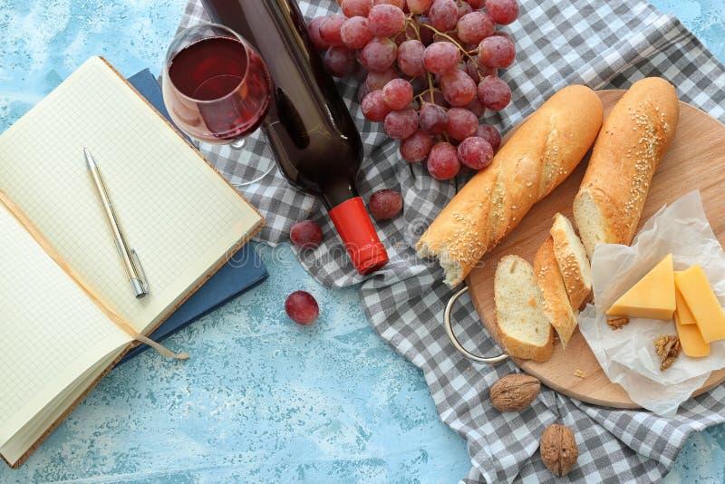 Composición con el vino tinto, el pan y el queso en la tabla imagen de archivo