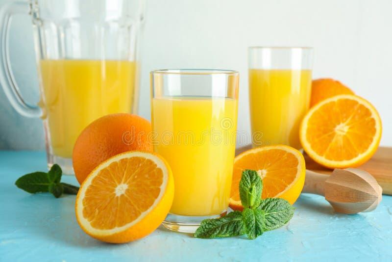 Composición con el zumo de naranja fresco en cristalería, menta y juicer de madera en la tabla de color contra el fondo blanco, p foto de archivo