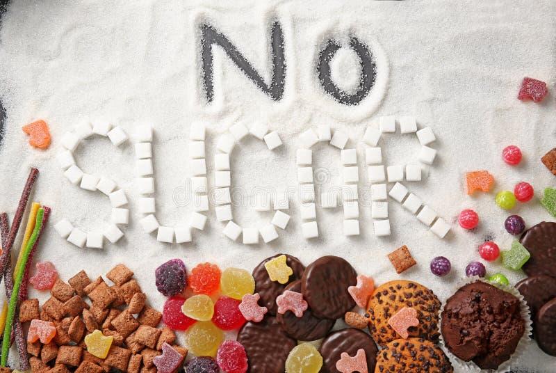 Composición con frase NINGÚN AZÚCAR y dulces en la arena del azúcar imágenes de archivo libres de regalías