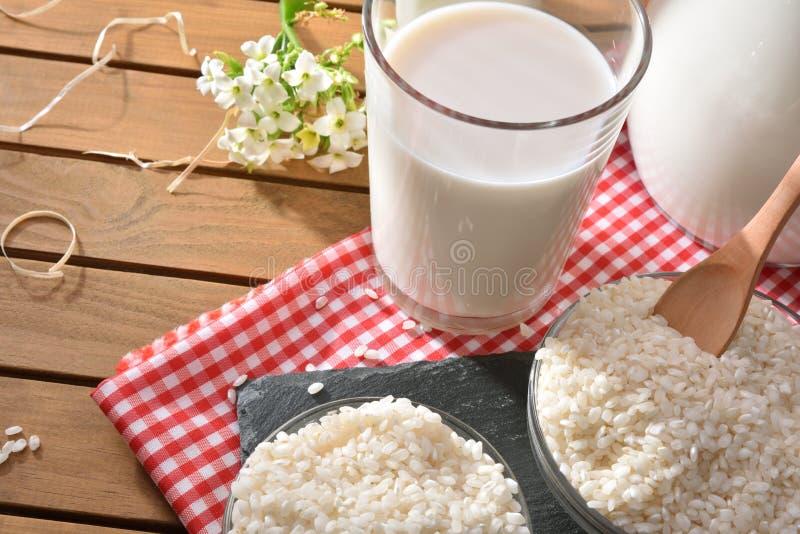 Composición con la bebida del arroz en envases en el campo elevado foto de archivo