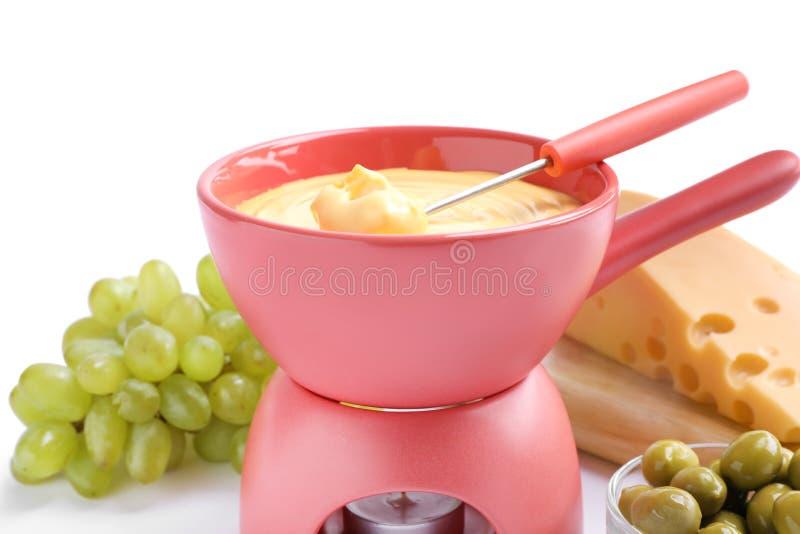 Composición con la 'fondue', las uvas y las aceitunas deliciosas de queso en el fondo blanco imágenes de archivo libres de regalías