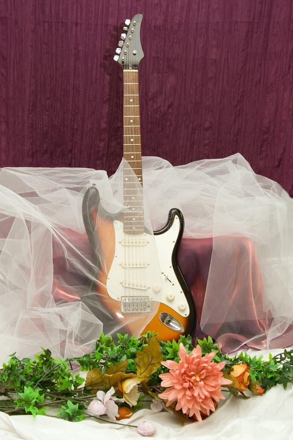 Composición con la guitarra y las flores foto de archivo