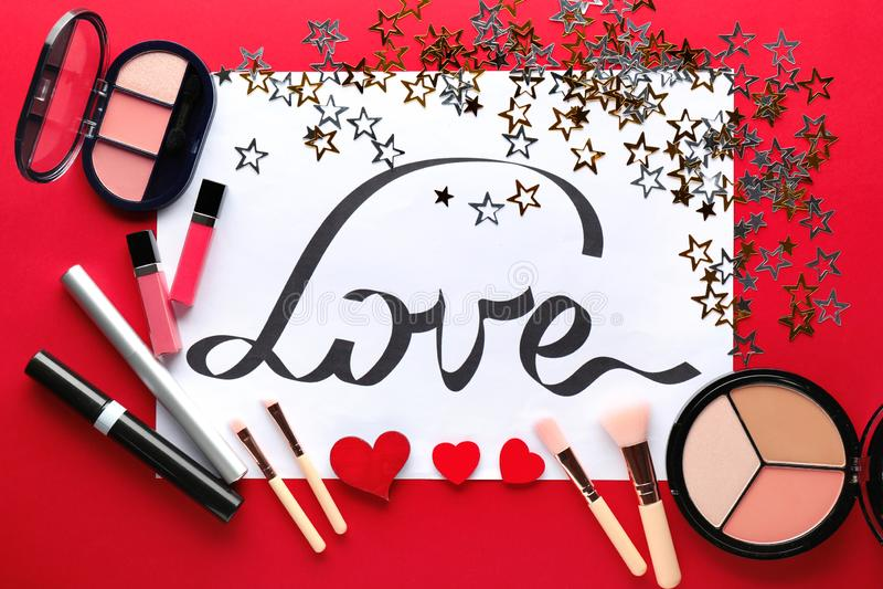 Composición con la palabra AMOR y cosméticos decorativos en fondo del color fotos de archivo libres de regalías