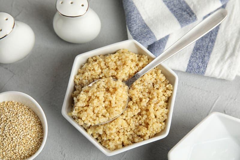 Composición con la quinoa cocinada en el cuenco de cerámica blanco en la tabla imágenes de archivo libres de regalías