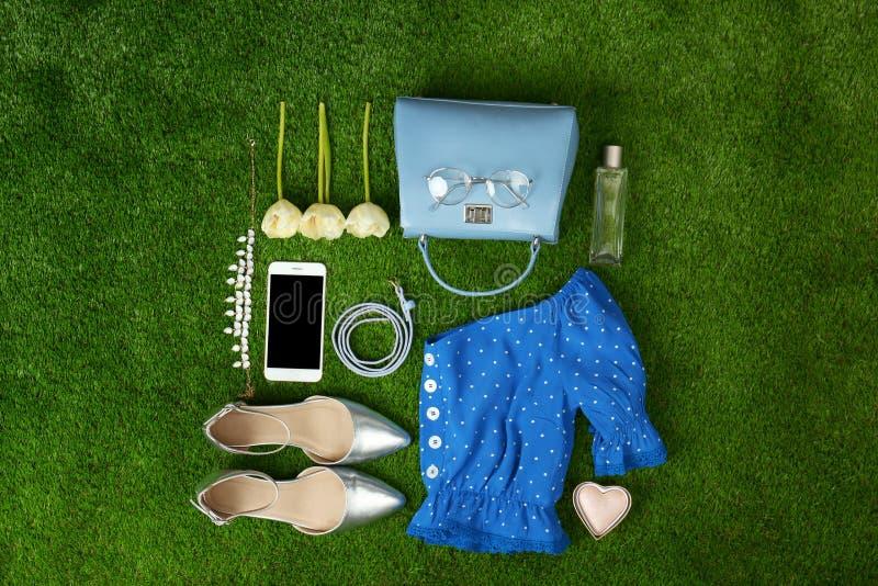 Composici?n con la ropa y los accesorios de la primavera de las mujeres elegantes en la hierba verde, endecha plana imágenes de archivo libres de regalías