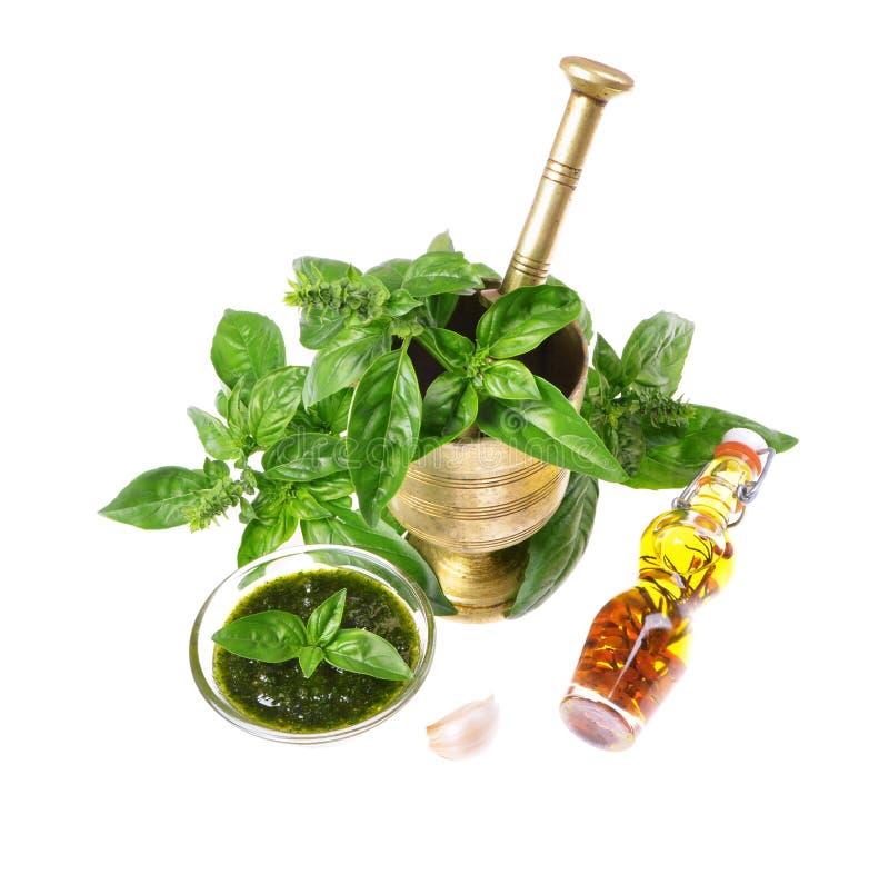 Composición con la salsa verde del pesto en el buque, las hojas de la albahaca y el ajo de cristal imagen de archivo