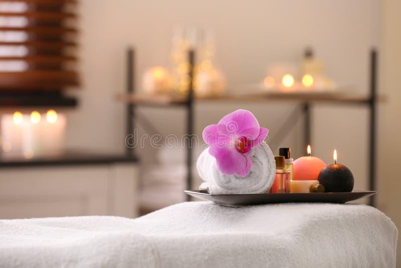 Composición con la toalla, las velas y los aceites en la tabla del masaje en salón del balneario fotografía de archivo