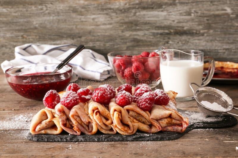Composición con las crepes finas sabrosas, las bayas, el jarro de leche y el atasco en la tabla de madera fotos de archivo libres de regalías