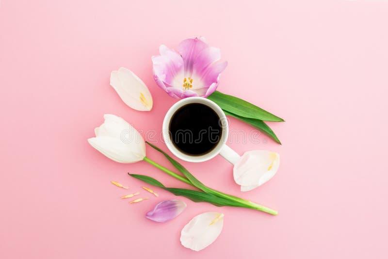 Composición con las flores, los pétalos y la taza de café sólo en fondo en colores pastel rosado Endecha plana, visión superior fotografía de archivo