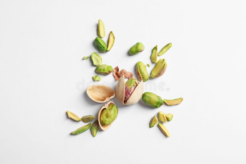 Composición con las nueces de pistacho orgánicas en el fondo blanco fotografía de archivo