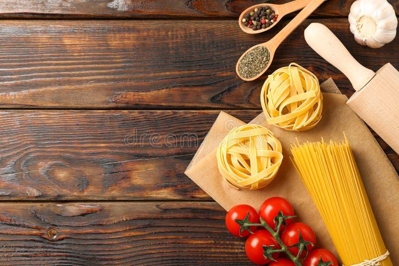 Composición con las pastas, los tomates, el rodillo, el ajo y especias en fondo de madera imágenes de archivo libres de regalías
