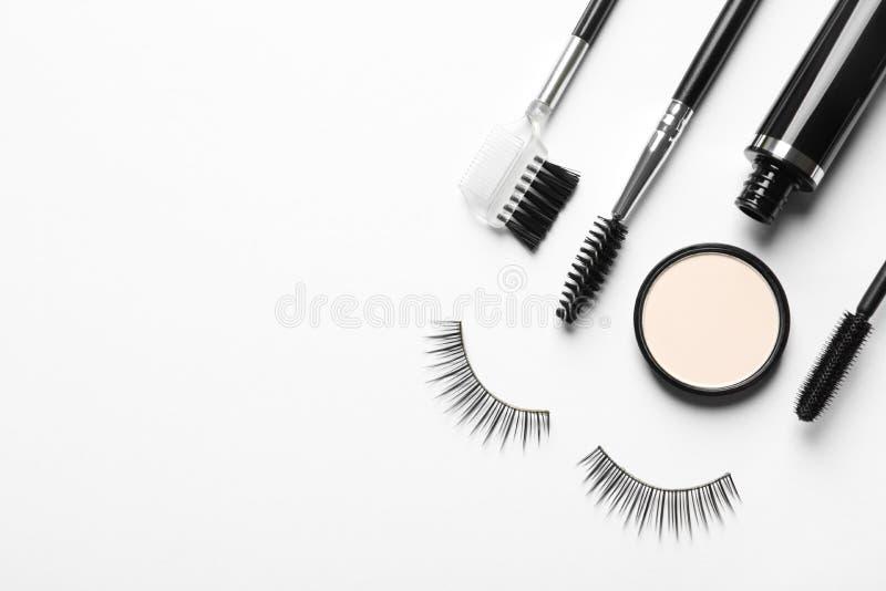 Composición con las pestañas falsas y otros productos de maquillaje en el fondo blanco imágenes de archivo libres de regalías