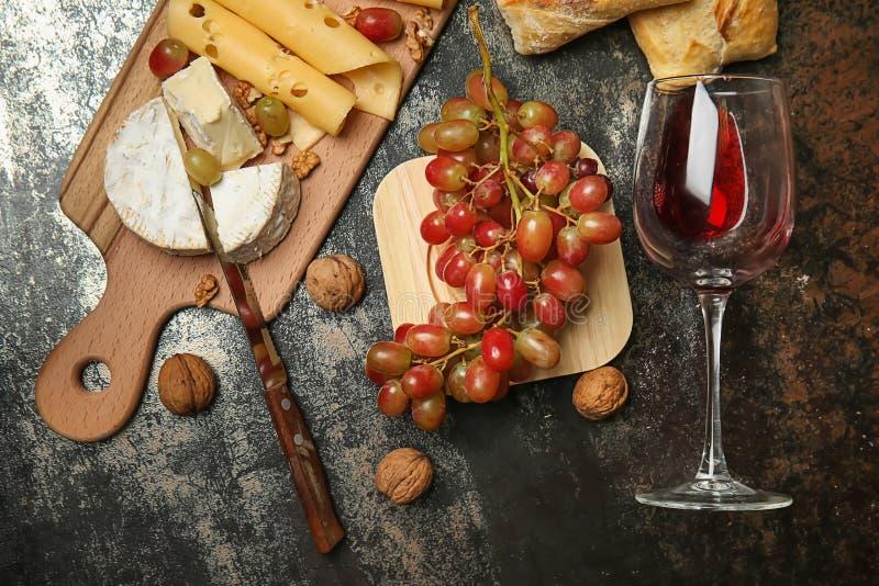 Composición con las uvas dulces, el vidrio de vino tinto y los bocados en la tabla fotos de archivo