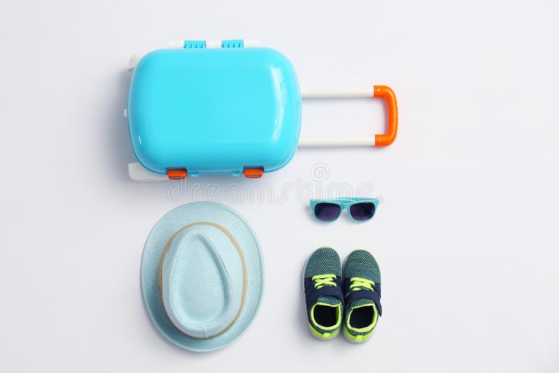 Composición con los accesorios azules de la maleta y del niño en el fondo blanco, visión superior Verano fotos de archivo