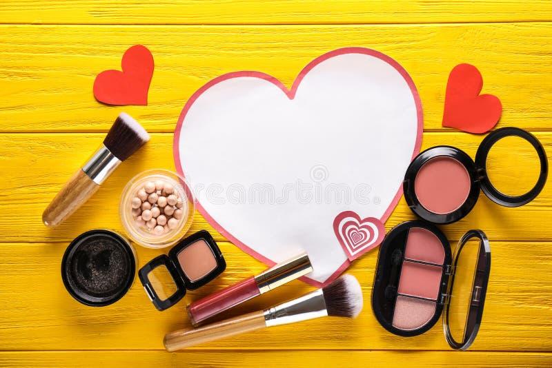 Composición con los corazones de papel y los cosméticos decorativos en fondo de madera del color fotos de archivo