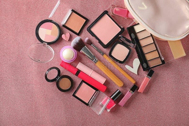 Composición con los cosméticos decorativos y bolso en fondo del color foto de archivo