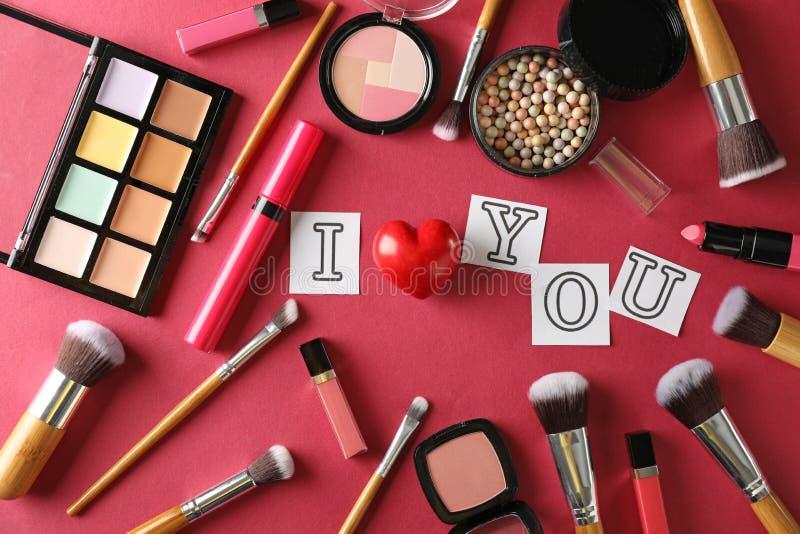 Composición con los cosméticos decorativos y frase TE AMO en fondo del color imágenes de archivo libres de regalías