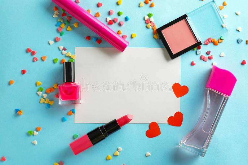 Composición con los cosméticos, la hoja de papel y los corazones decorativos en fondo del color imagen de archivo