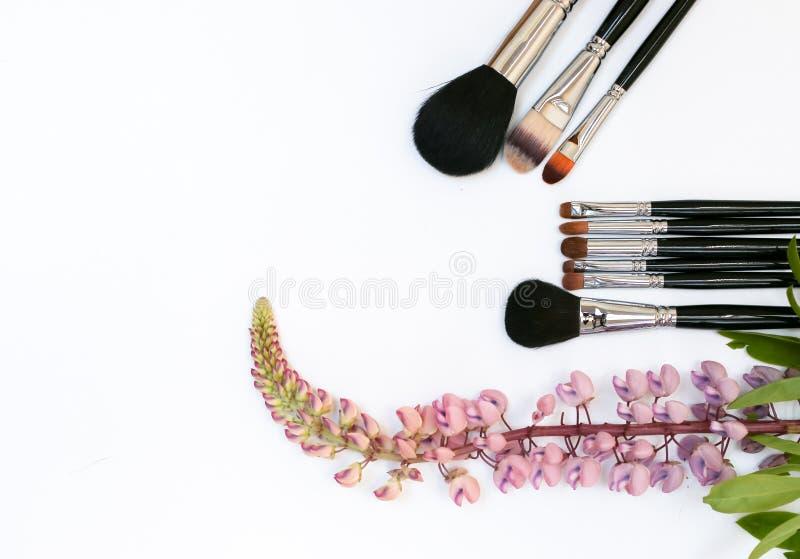 Composición con los cosméticos, los cepillos, y las flores del maquillaje en el fondo blanco fotos de archivo