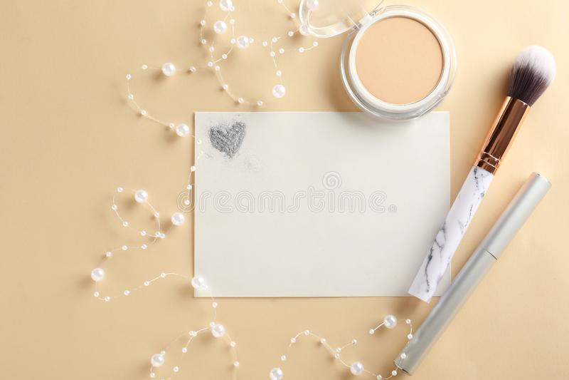 Composición con los cosméticos y la hoja de papel decorativos en fondo del color imagen de archivo libre de regalías