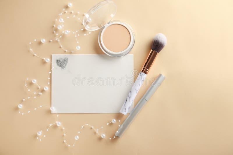Composición con los cosméticos y la hoja de papel decorativos en fondo del color fotos de archivo