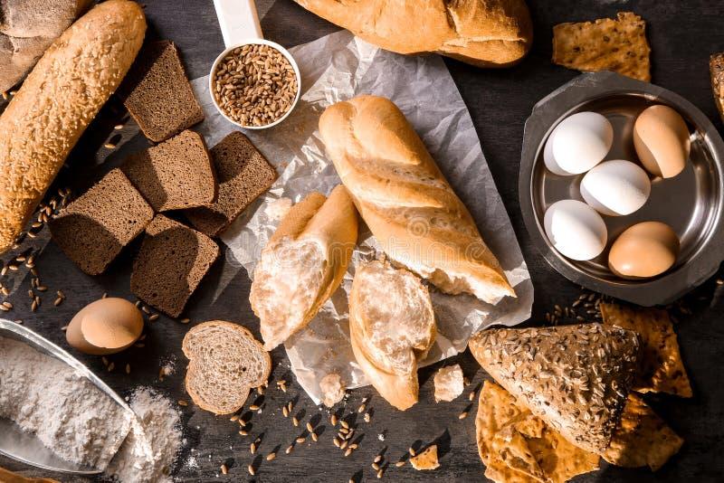 Composición con los diversos productos e ingredientes de la panadería en el fondo gris, visión superior foto de archivo