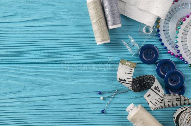 Composición con los hilos y los accesorios de costura en fondo azul imagen de archivo