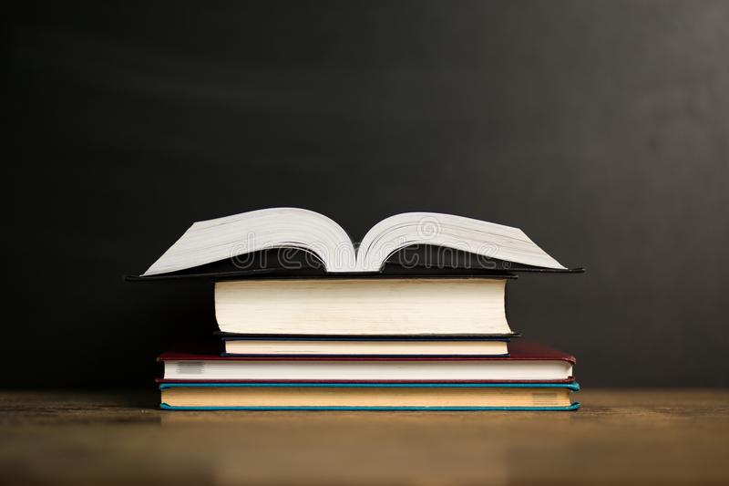 Composición con los libros viejos del libro encuadernado, el diario en la tabla de madera de la cubierta y el fondo oscuro De nue foto de archivo libre de regalías