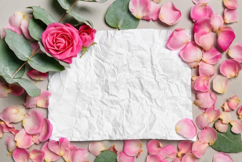 Composición con los pétalos color de rosa rosados hermosos y tarjeta de papel arrugado en fondo gris fotografía de archivo