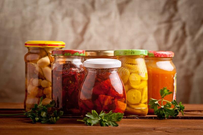 Composición con los tarros de verduras conservadas en vinagre. fotografía de archivo