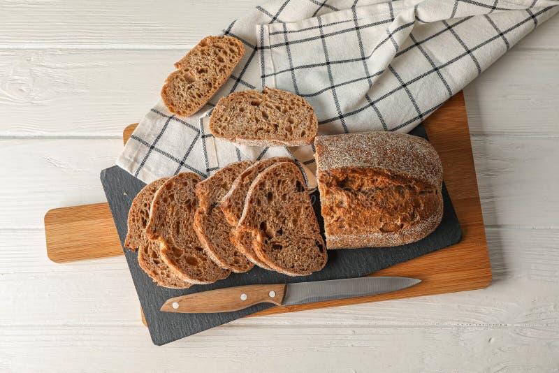 Composición con pan, el cuchillo, la toalla de cocina y la tabla de cortar en el fondo de madera blanco, visión superior imágenes de archivo libres de regalías