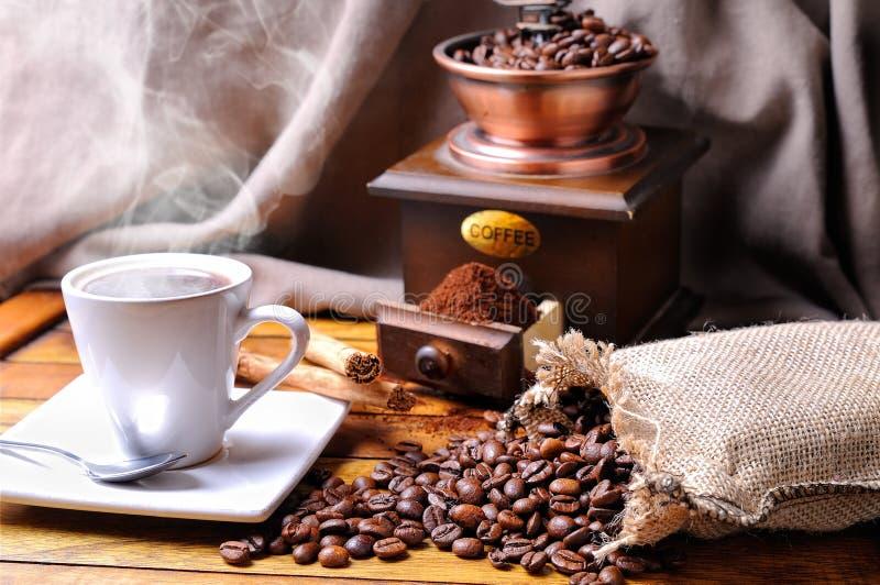 Composición con una taza de café, habas y amoladora de café foto de archivo libre de regalías