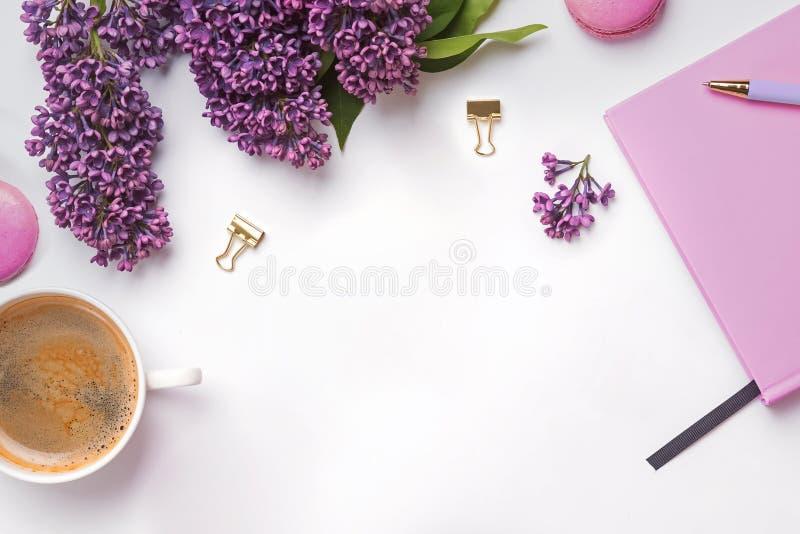 Composición creativa con accesorios femeninos, bellas flores de lilaco, café y macarons imagenes de archivo