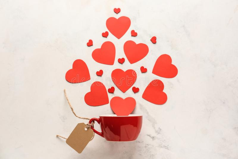 Composición creativa con los corazones que caen en taza en fondo ligero Celebraci?n del d?a de tarjetas del d?a de San Valent?n fotos de archivo